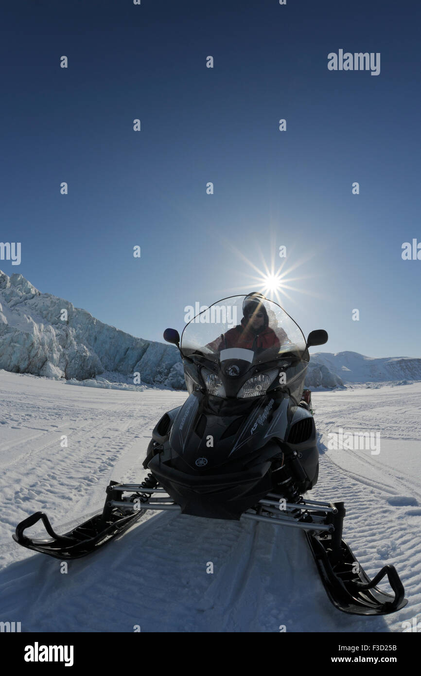 Expedition member driving with ski doo over ice from frozen sea with glacier and sun in background, Von Postbreen, - Stock Image