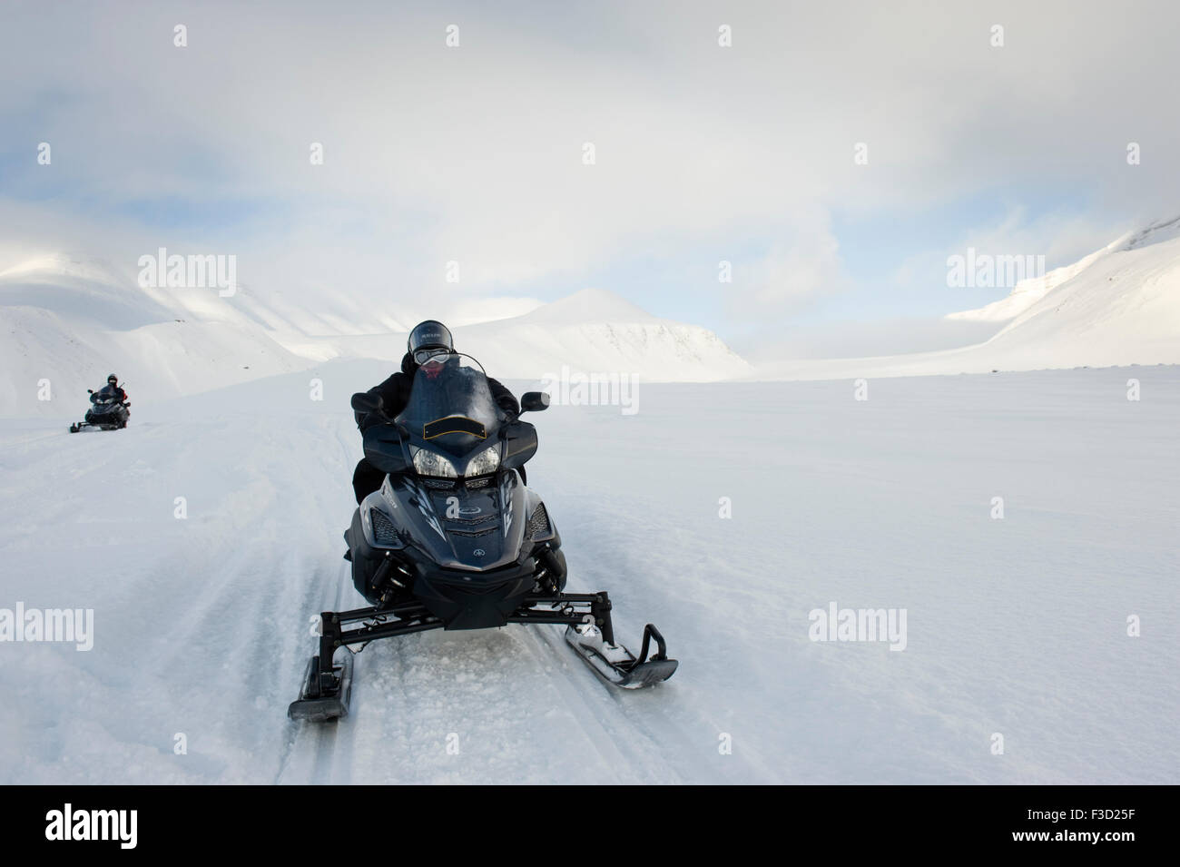Man on snowmobile on it's way in a snowcovered landscape with glacier behind, Semmeldalen, Spitsbergen, Svalbard, - Stock Image