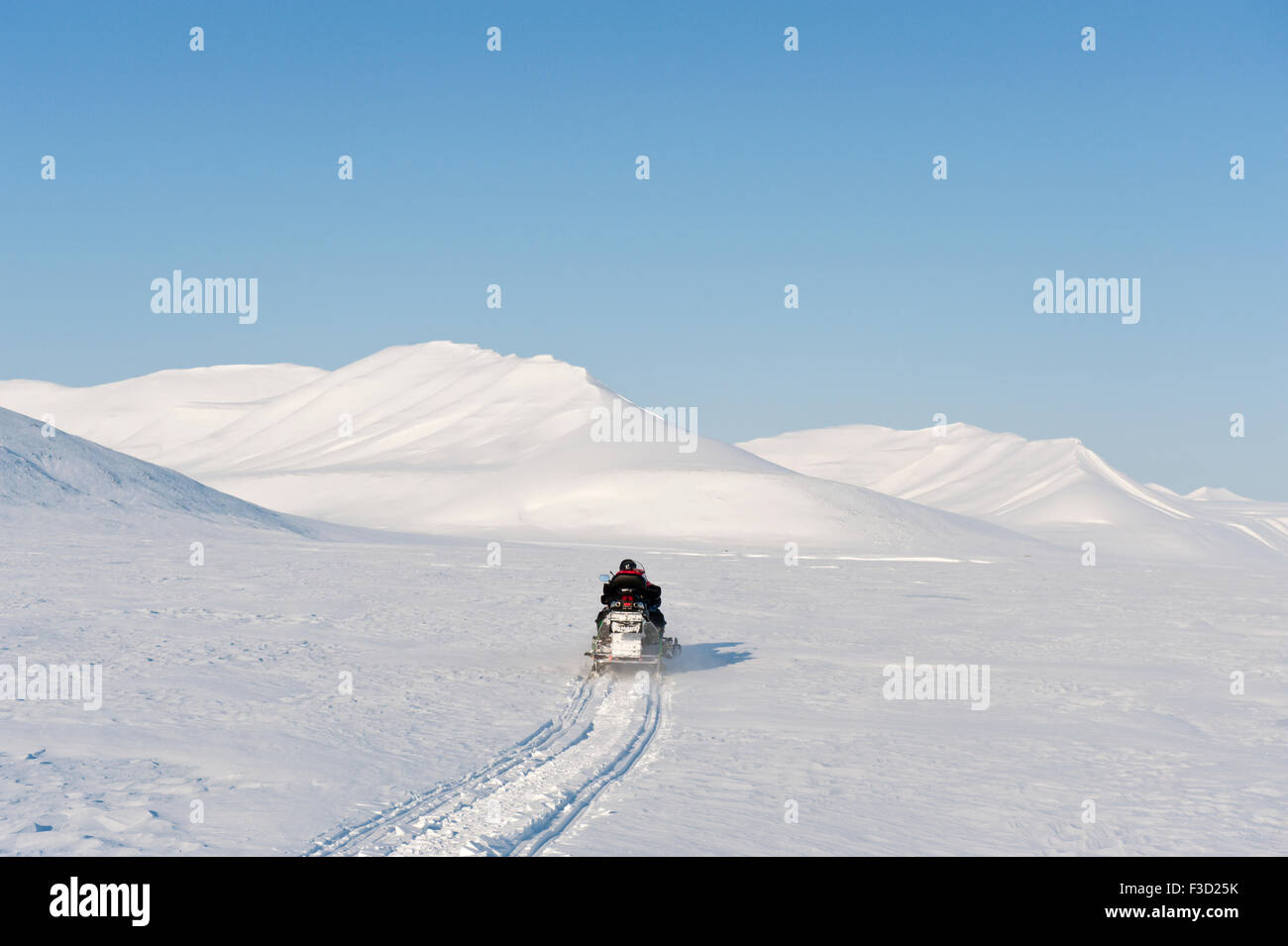 Man on snowmobile on it's way in a snowcovered landscape, Spitsbergen, Svalbard, Norway. - Stock Image