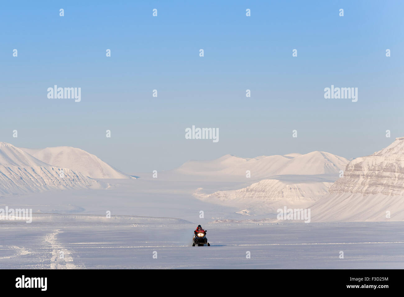 Man on snowmobile on it's way in a snowcovered landscape with Tunabreen glacier behind, Tempelfjorden, Spitsbergen, - Stock Image