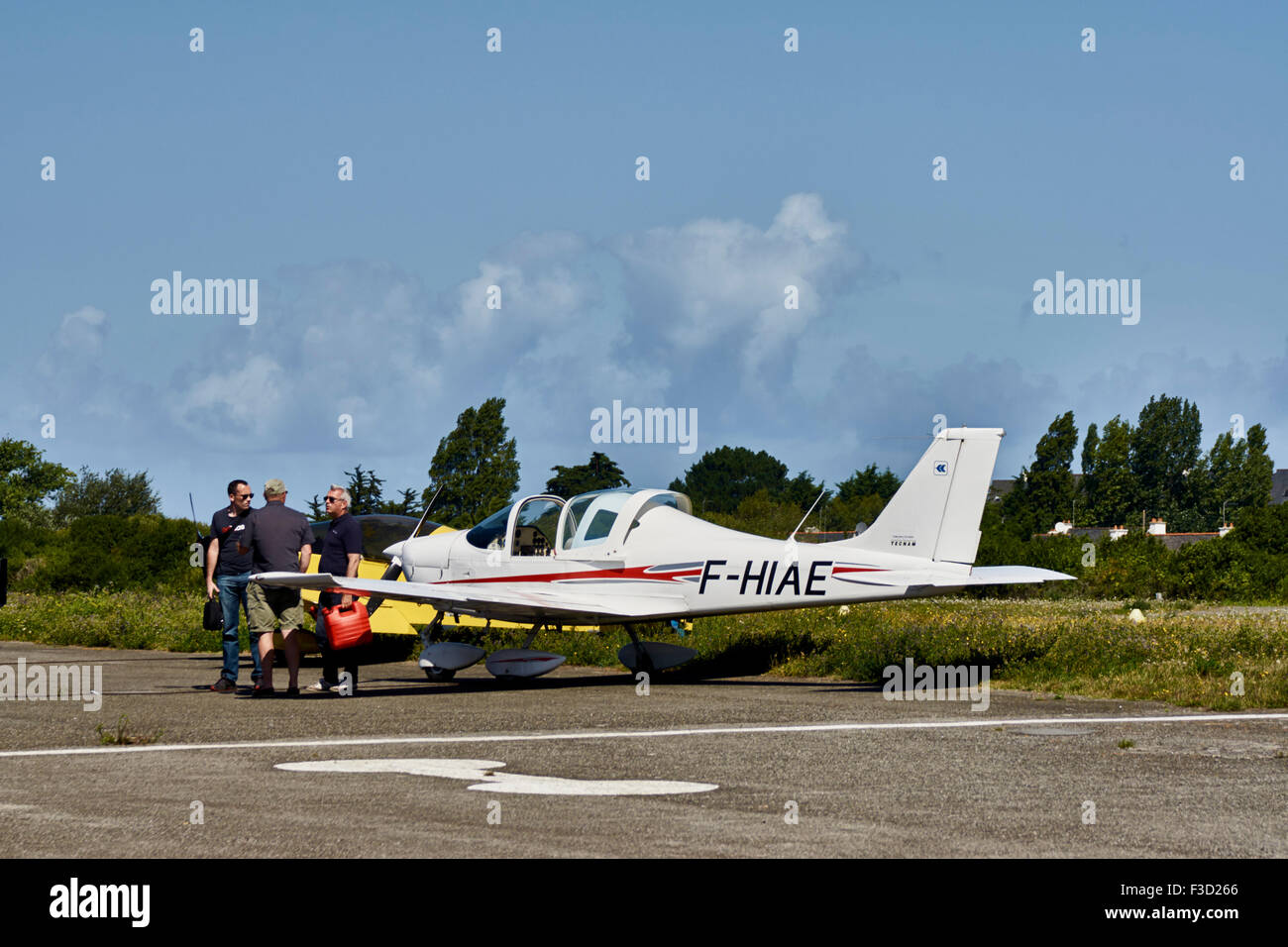Private aircraft on tarmac with three males standing alongside - Stock Image