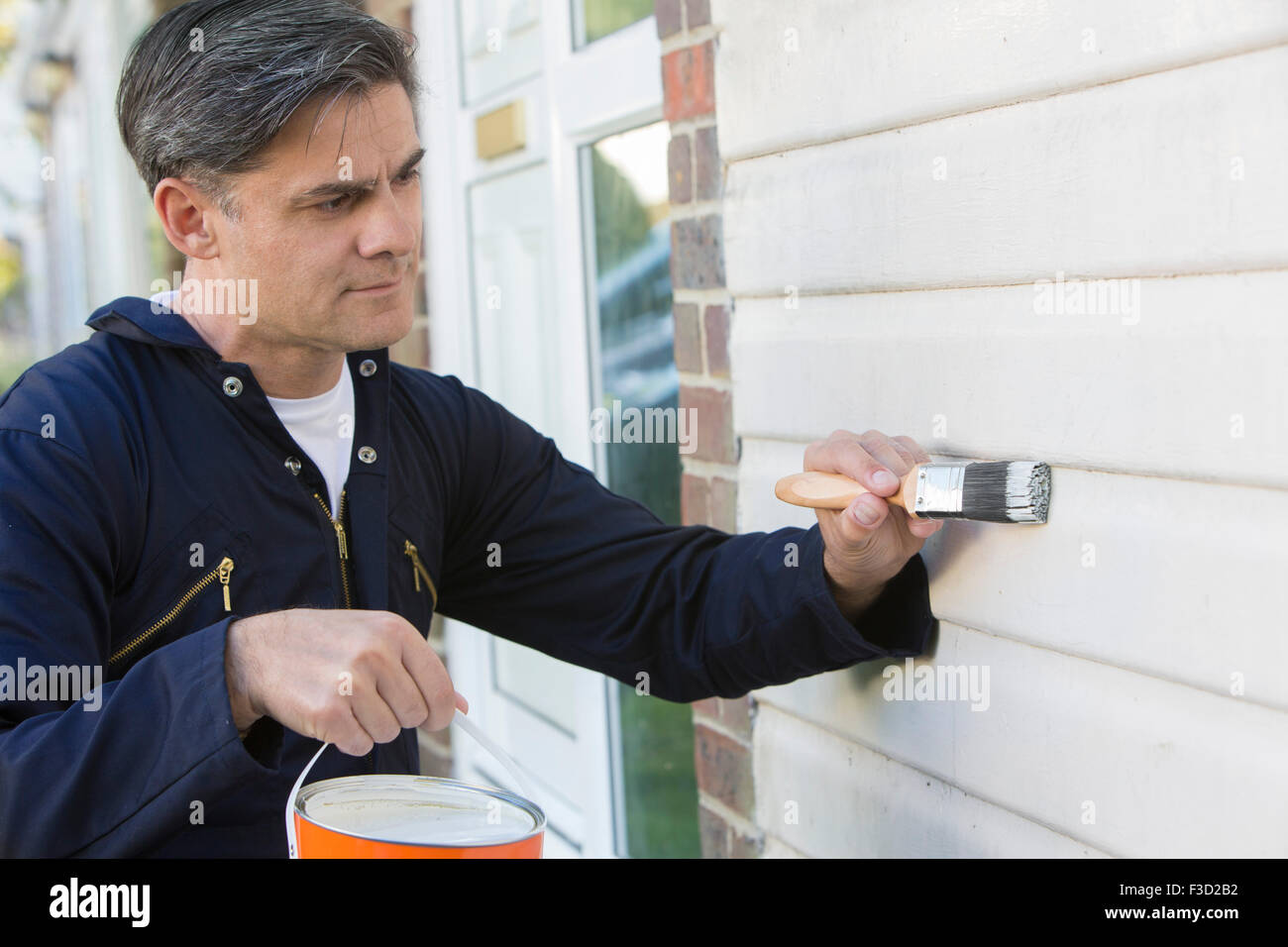 Man Holding Brush And Tin Painting Outside Of House - Stock Image