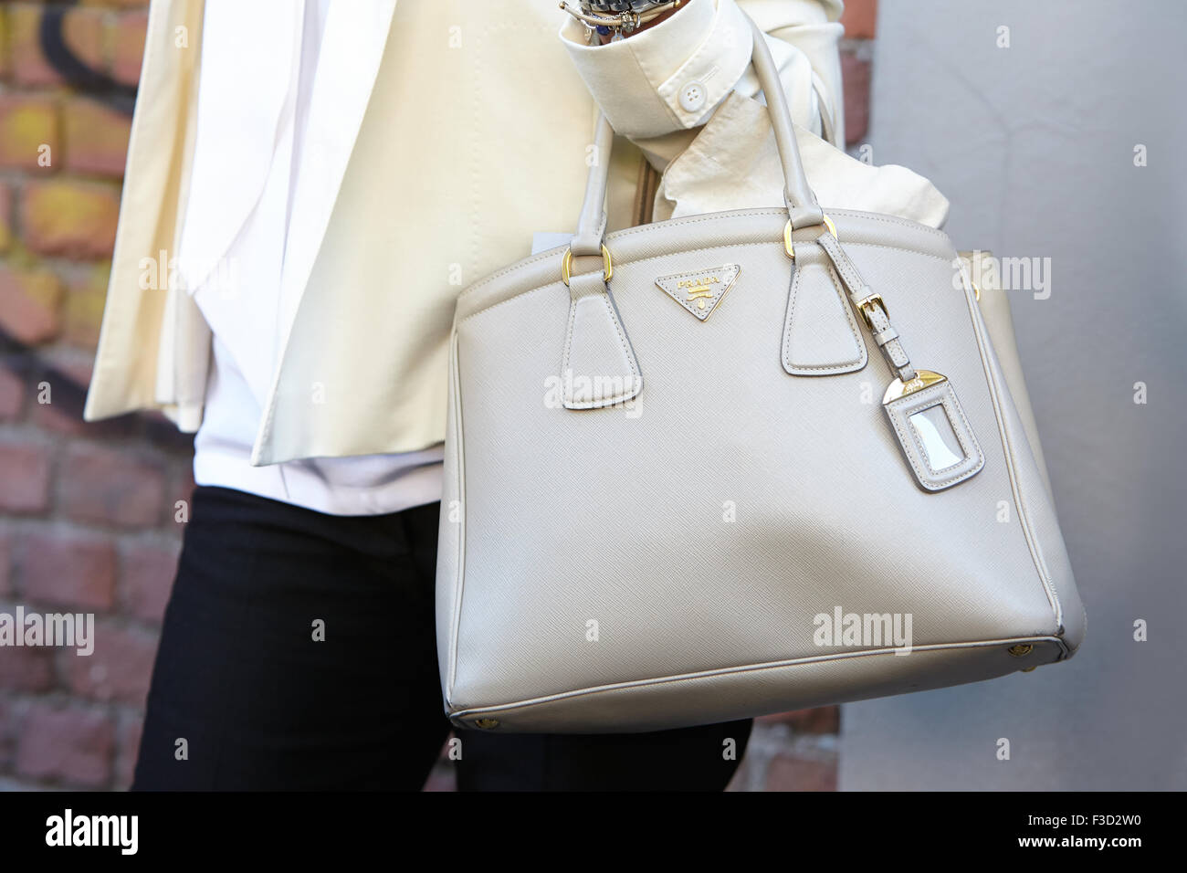 Woman poses for photographers before Fendi show with cream color Prada bag during Milan Fashion Week Day 2 Stock Photo