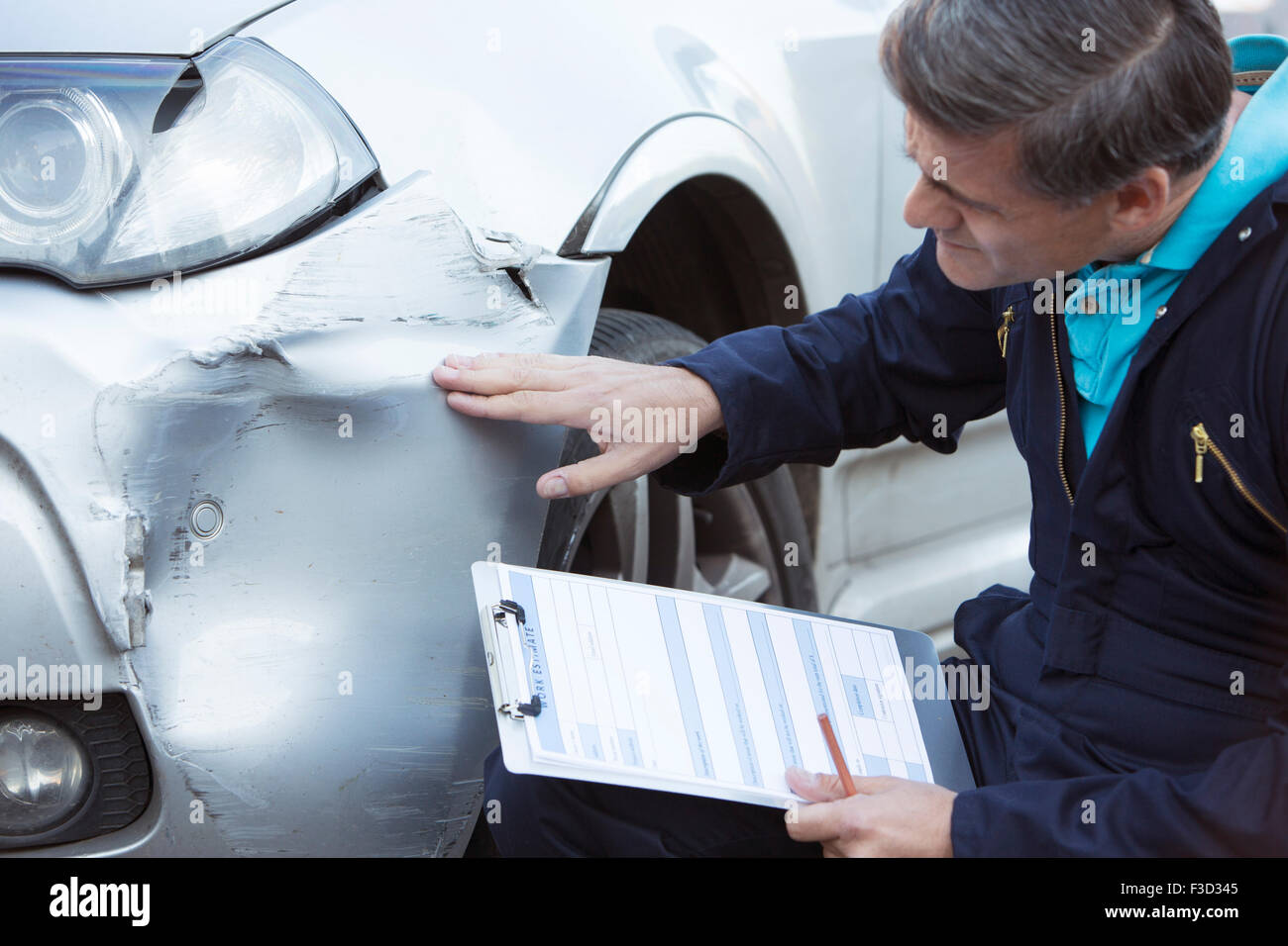 Auto Workshop Mechanic Inspecting Damage To Car And Filling In Repair Estimate - Stock Image