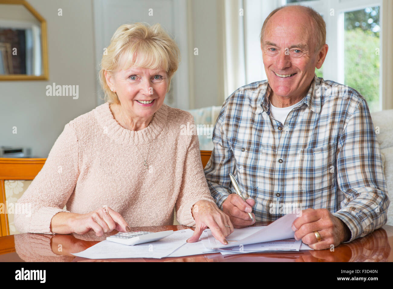 Happy Senior Couple reviewing Domestic Finances Together - Stock Image