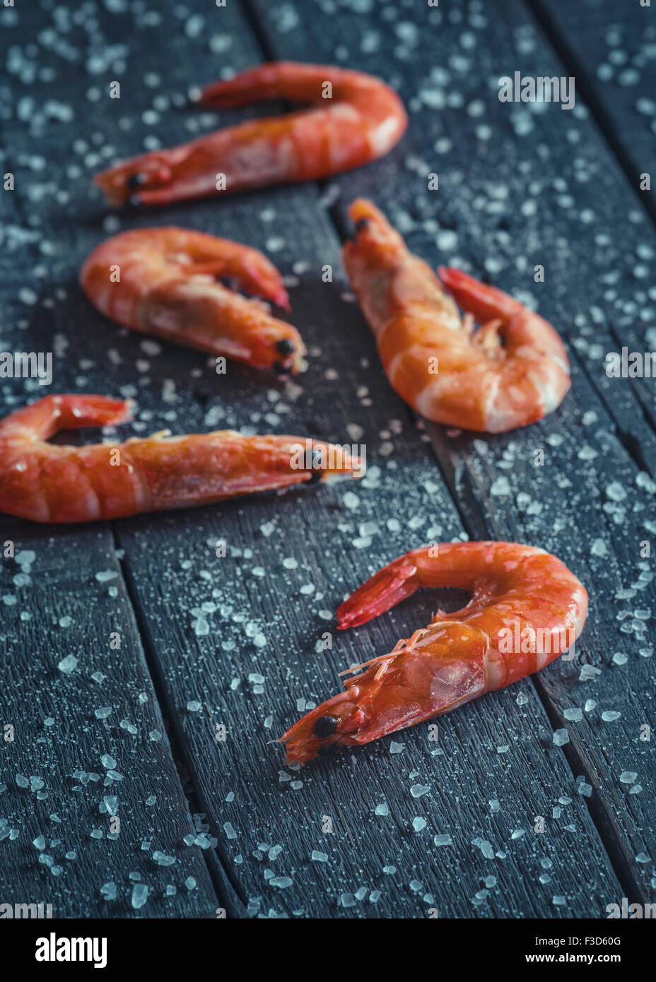 Some freshly caught prawns on a rustic table with rock salt - Stock Image