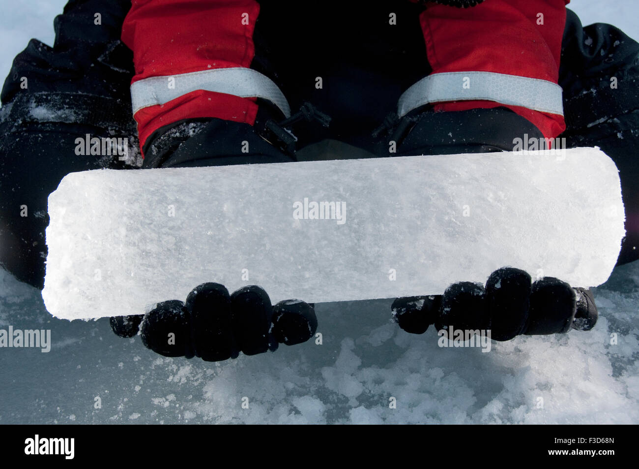 A scientist holds an ice core recently drilled from the Arctic Ocean icepack. - Stock Image