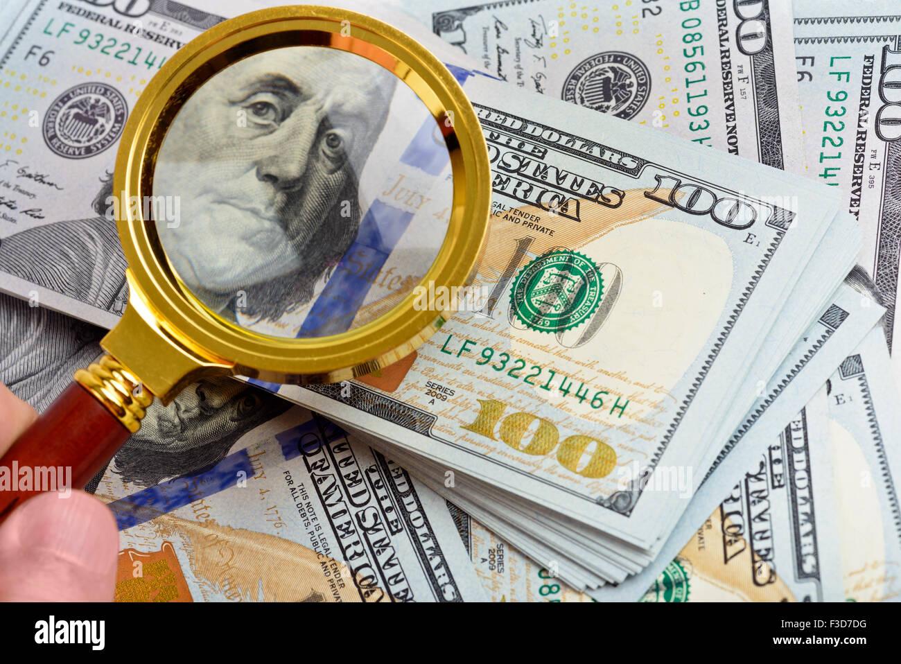 Hundred dollar banknotes under magnifying glass - Stock Image