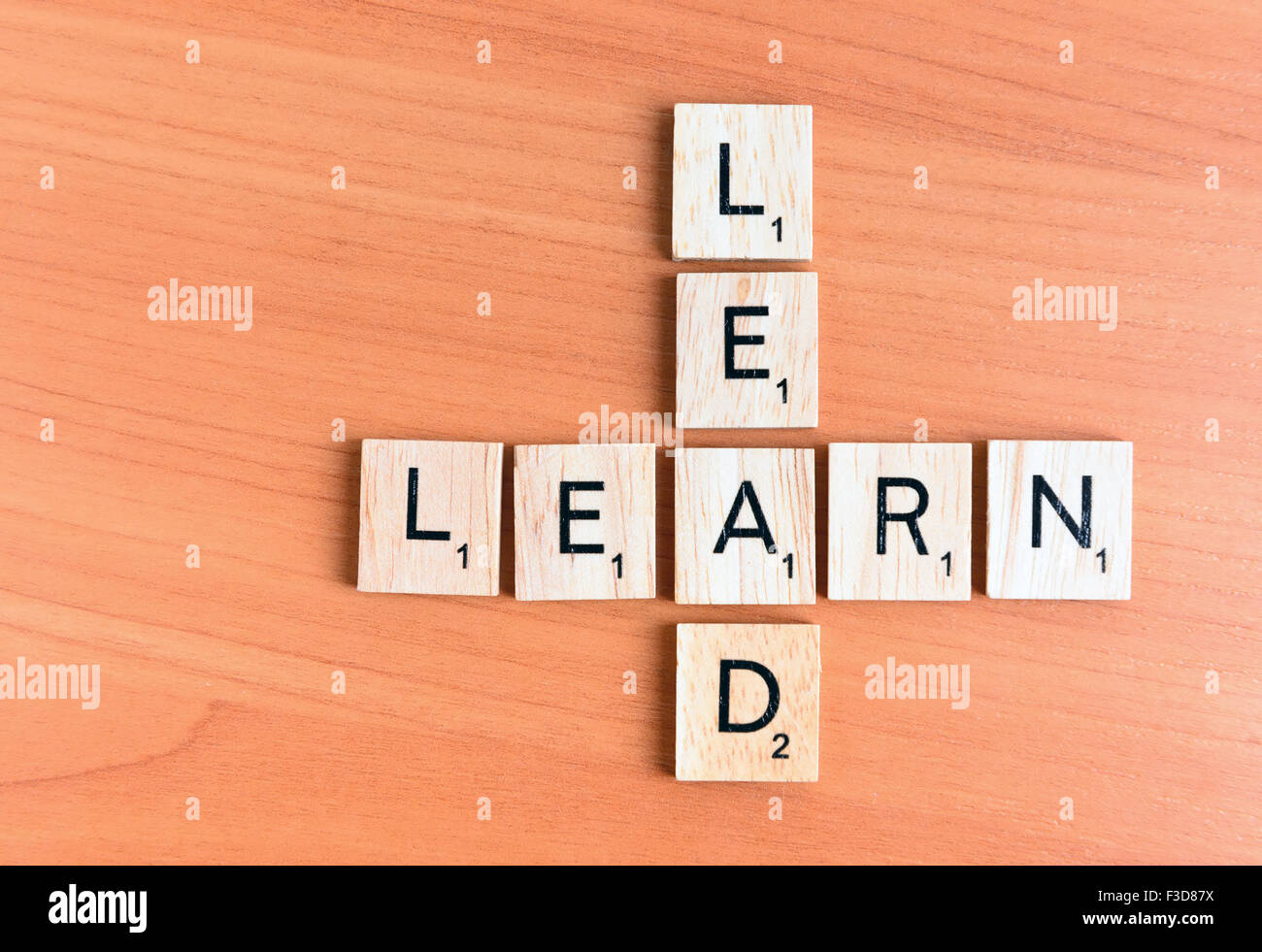 Learn and Lead text on a wooden background - Stock Image