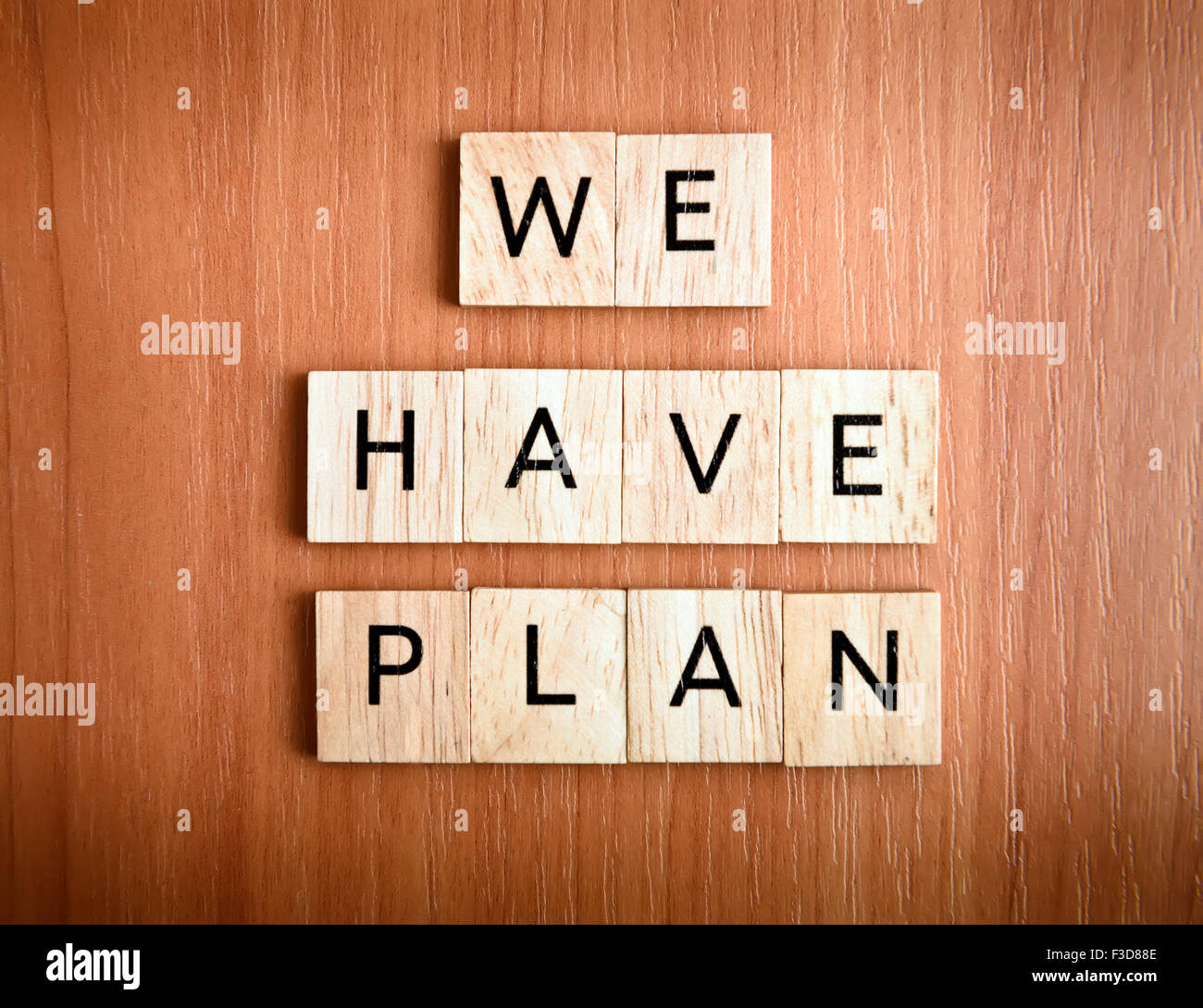 We have Plan text on tiles over wooden background - Stock Image