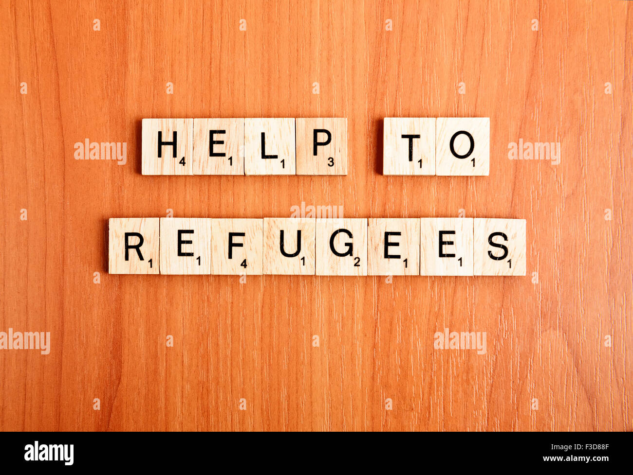 Refugees help text on wooden tiles letters - Stock Image