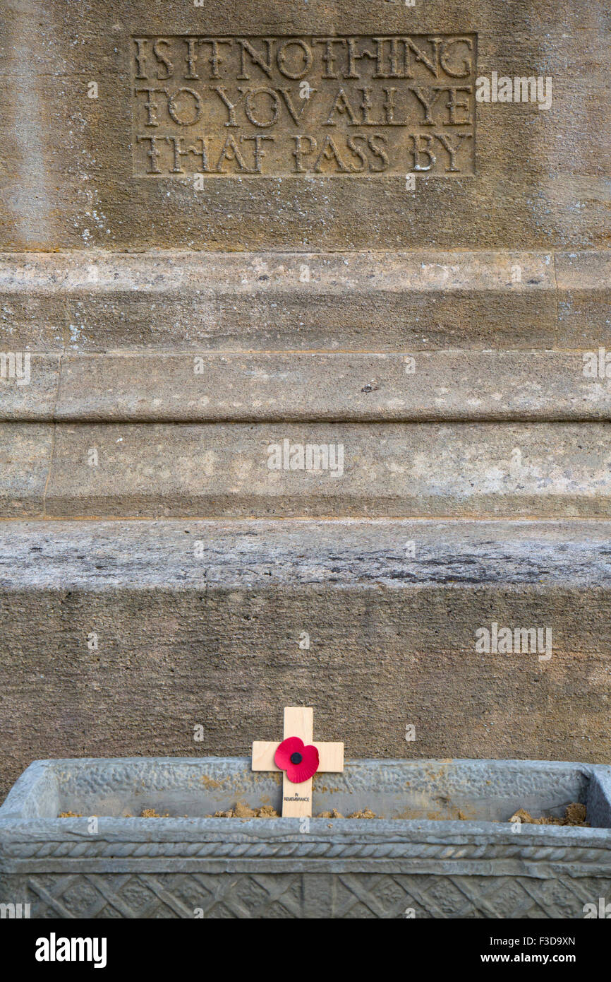 Single poppy and wooden cross on a War Memorial in an English town. - Stock Image