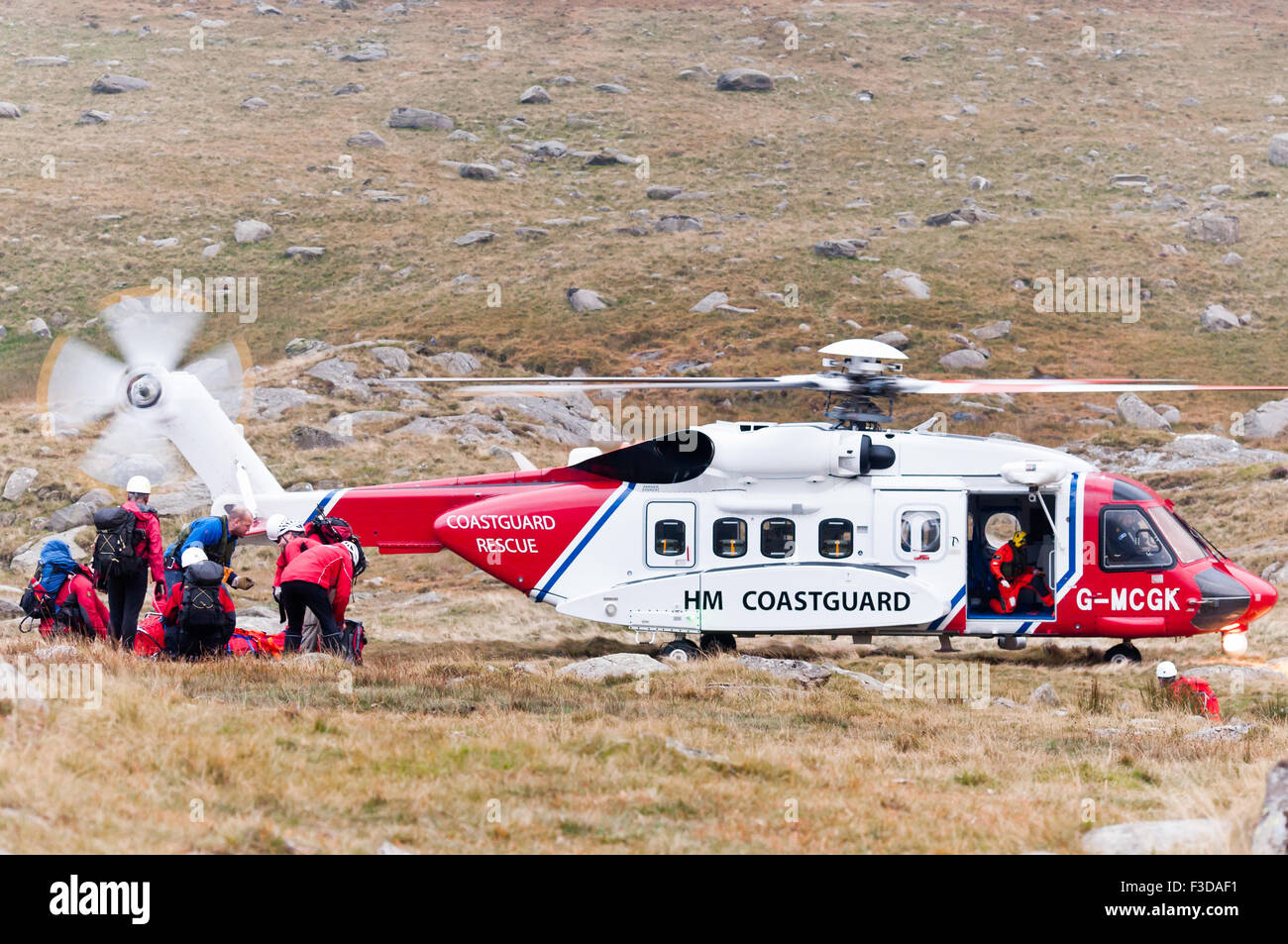 As dusk falls, Ogwen Valley Mountain Rescue Organisation prepare to take a casualty to the Coastguard Rescue Helicopter - Stock Image