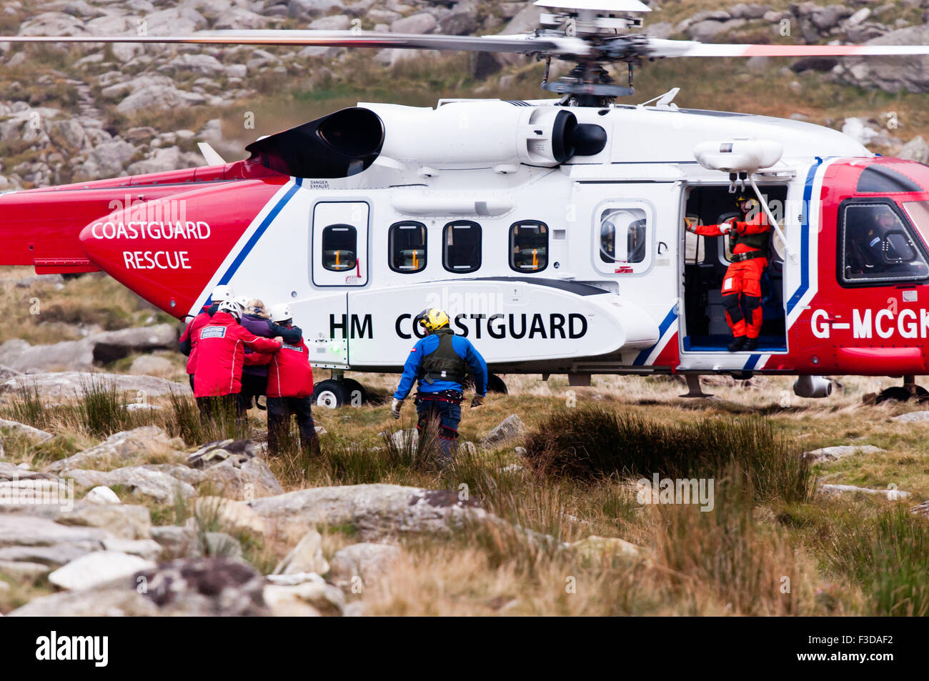 As dusk falls, Ogwen Valley Mountain Rescue Organisation personnel carry an injured walker to the local rescue helicopter - Stock Image