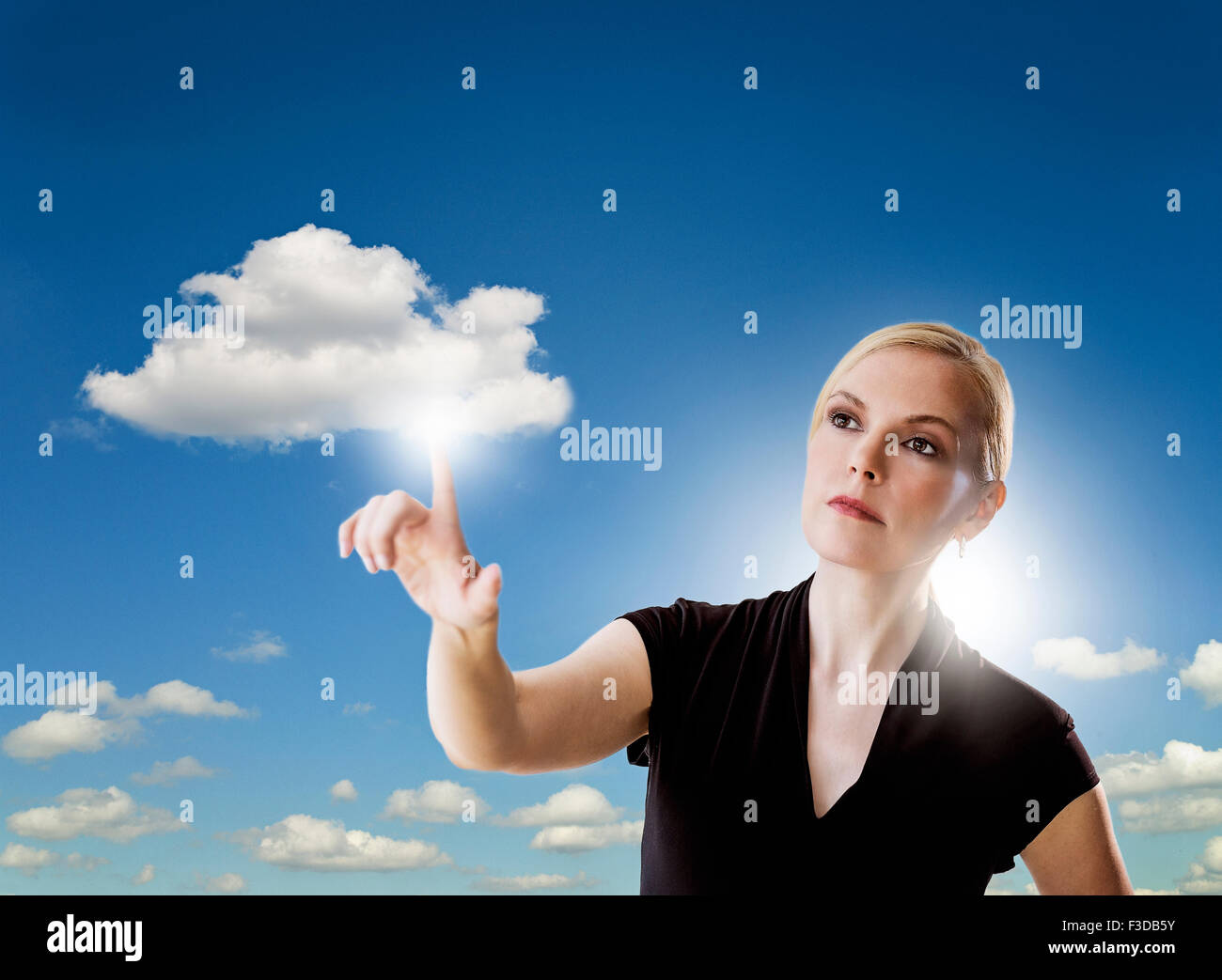 Portrait of woman touching cloud - Stock Image