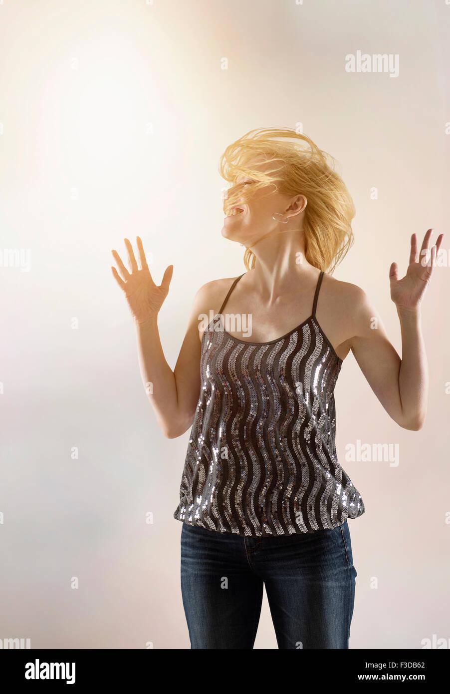 Happy woman dancing in studio - Stock Image