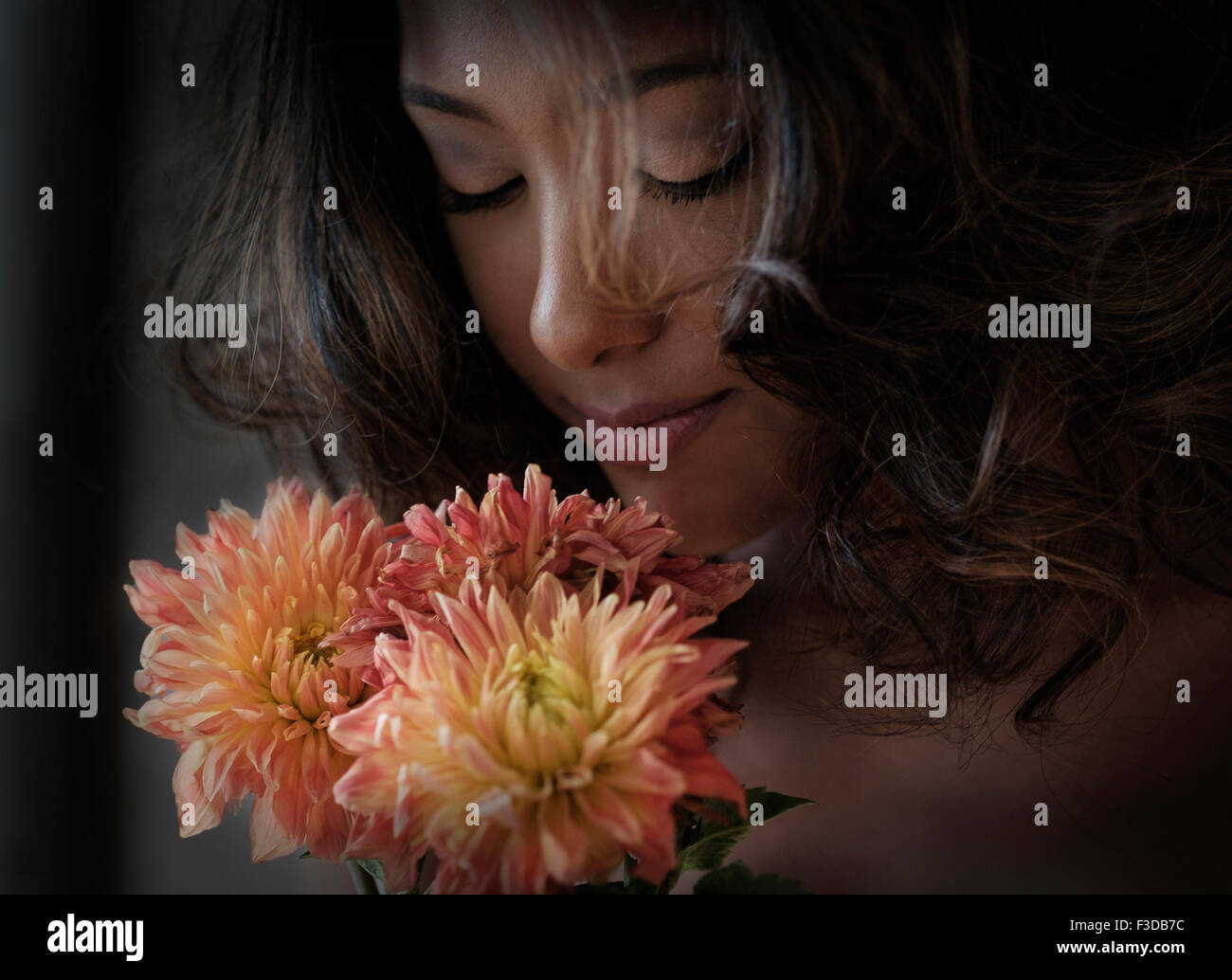Young woman smelling flowers - Stock Image