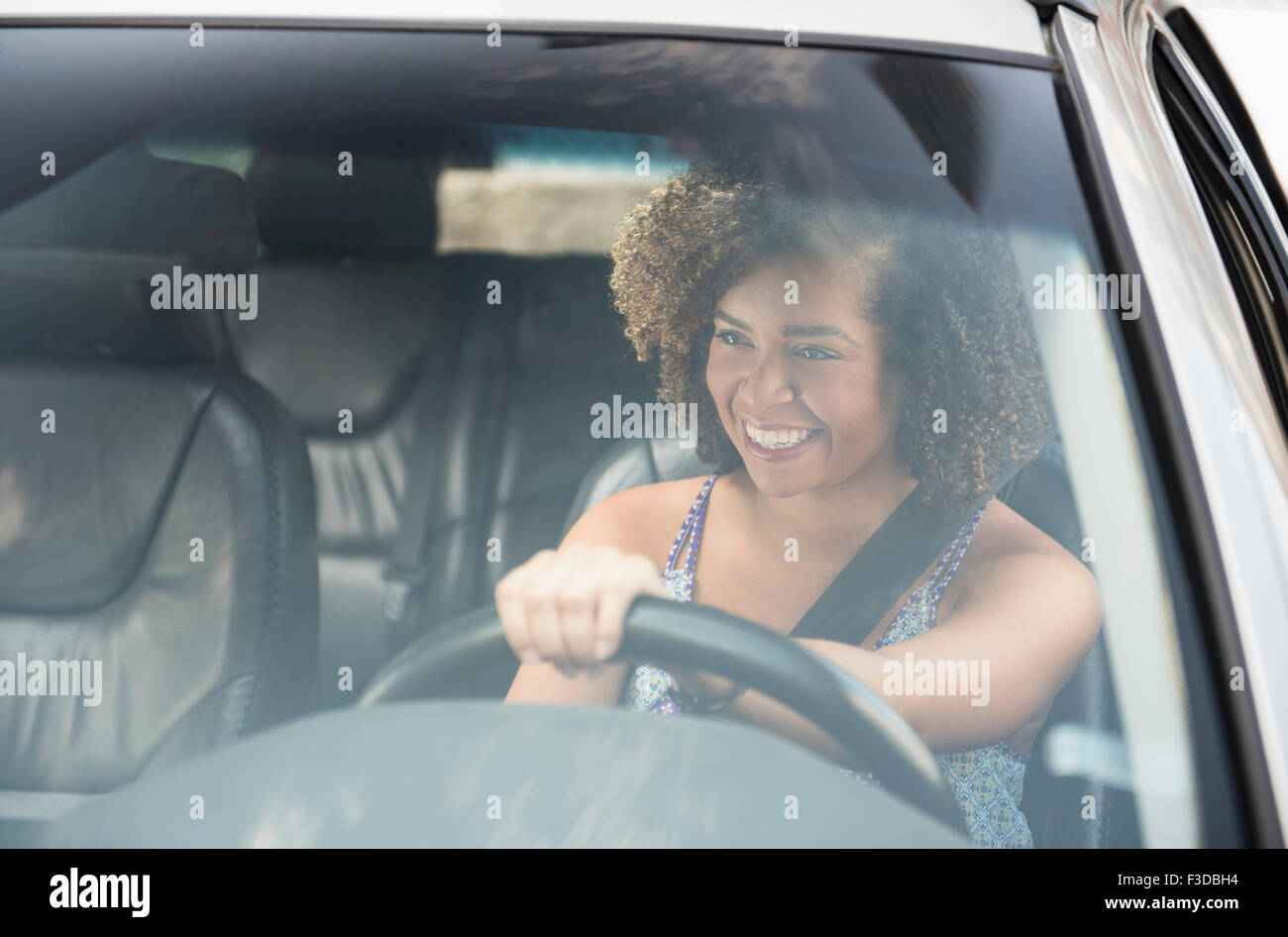 Young woman smiling while driving car - Stock Image