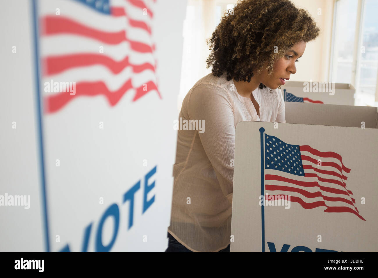 Young woman preparing voting booth - Stock Image