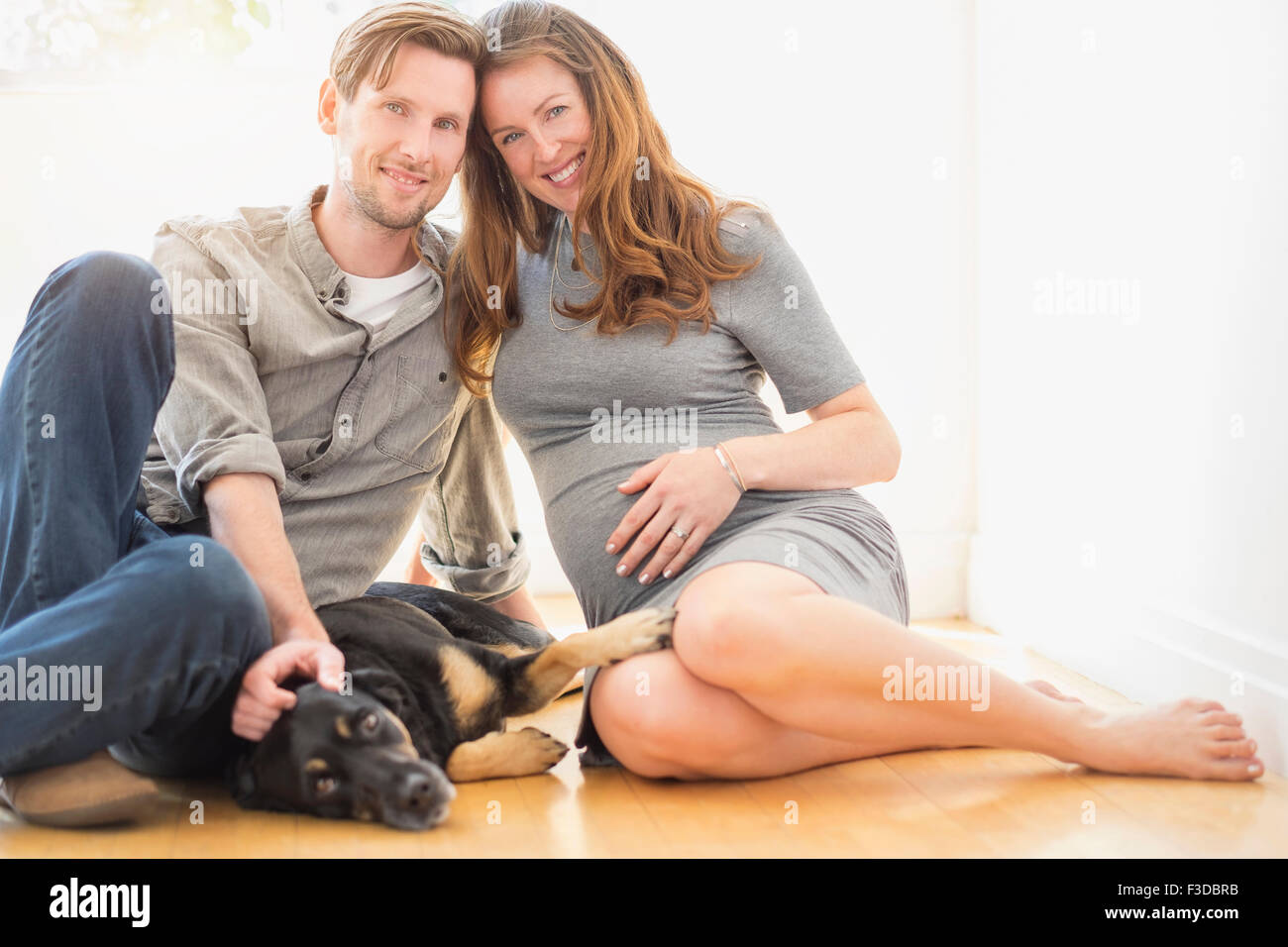 Portrait of mid-adult couple with dog indoors Stock Photo