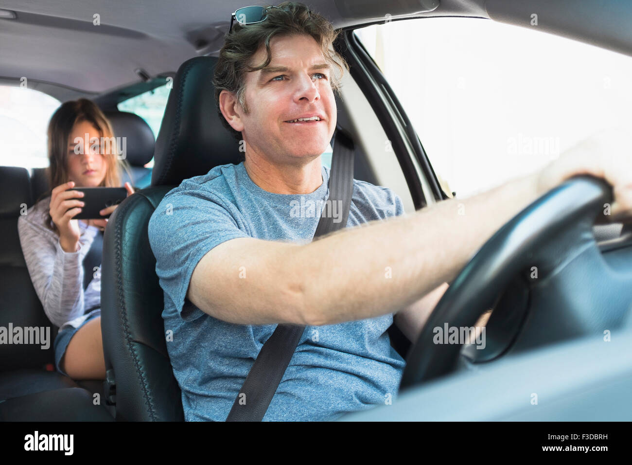 Man driving car, girl (10-11) texting in background - Stock Image