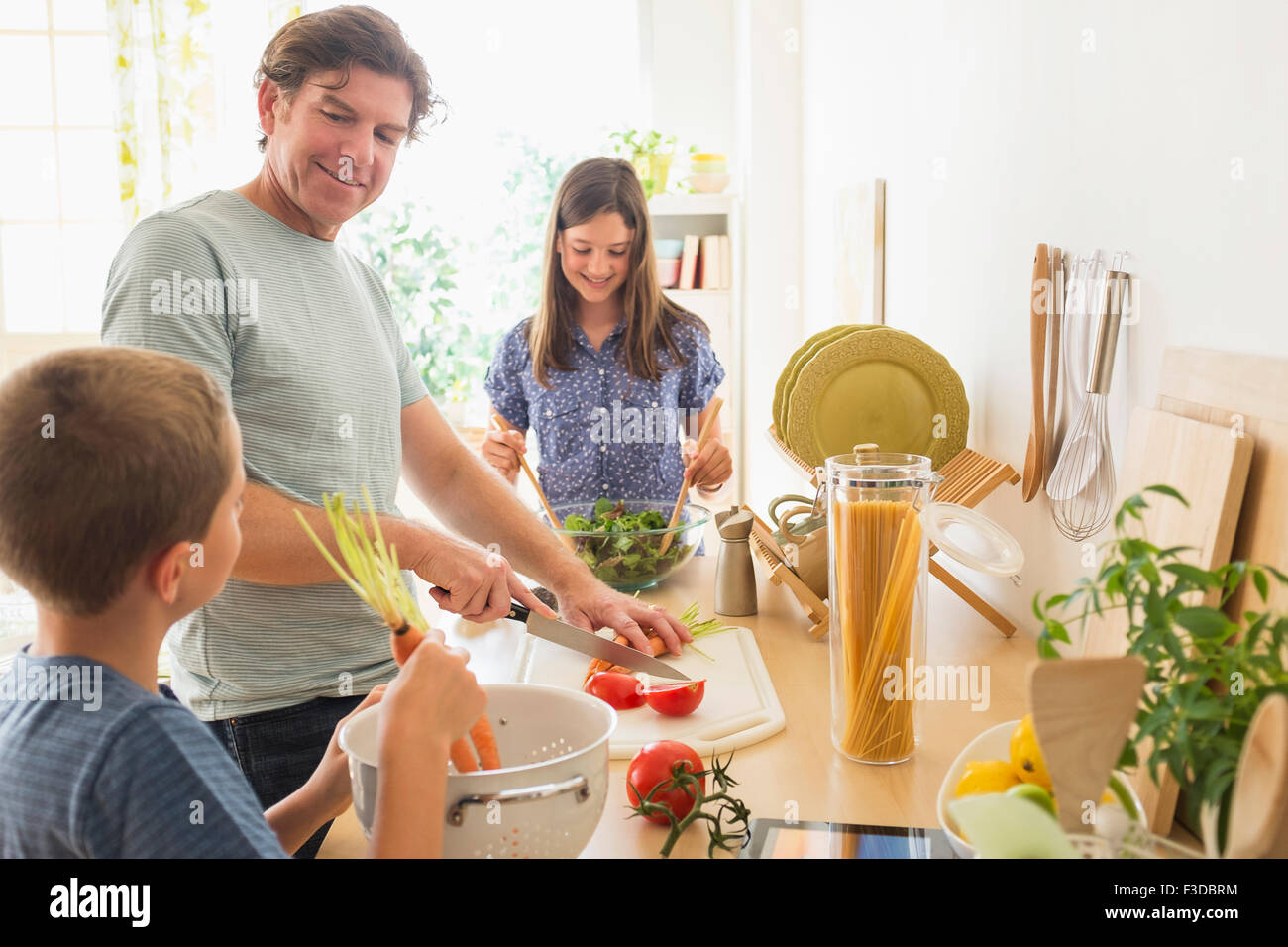Children (8-9, 10-11) preparing food with their father - Stock Image