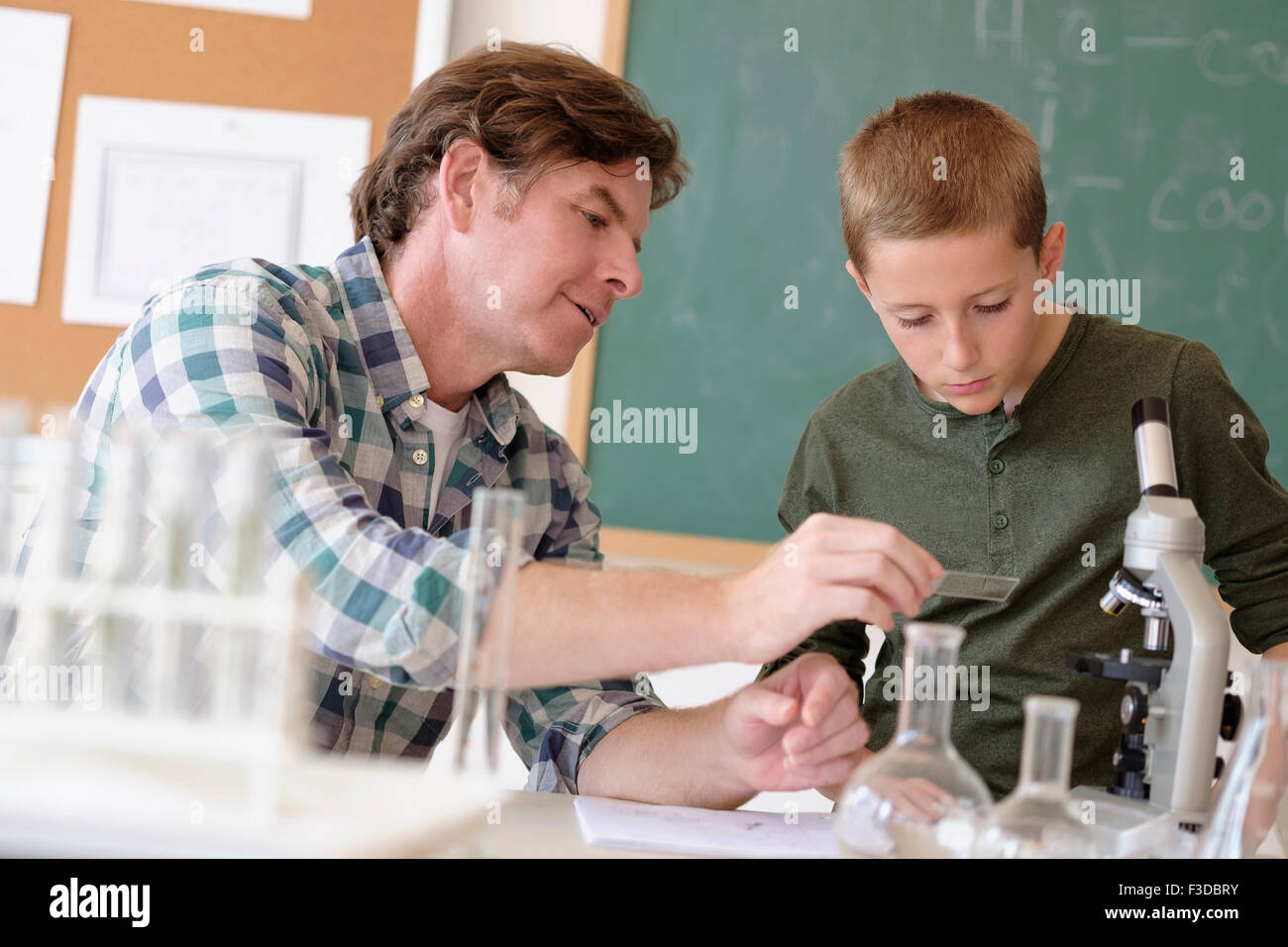 Teacher talking with student (8-9) in classroom - Stock Image