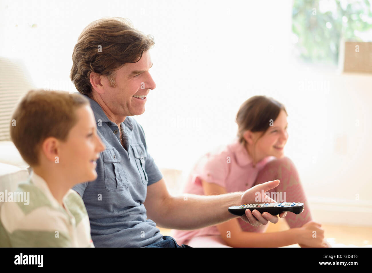Children (8-9, 10-11) watching TV with their father - Stock Image