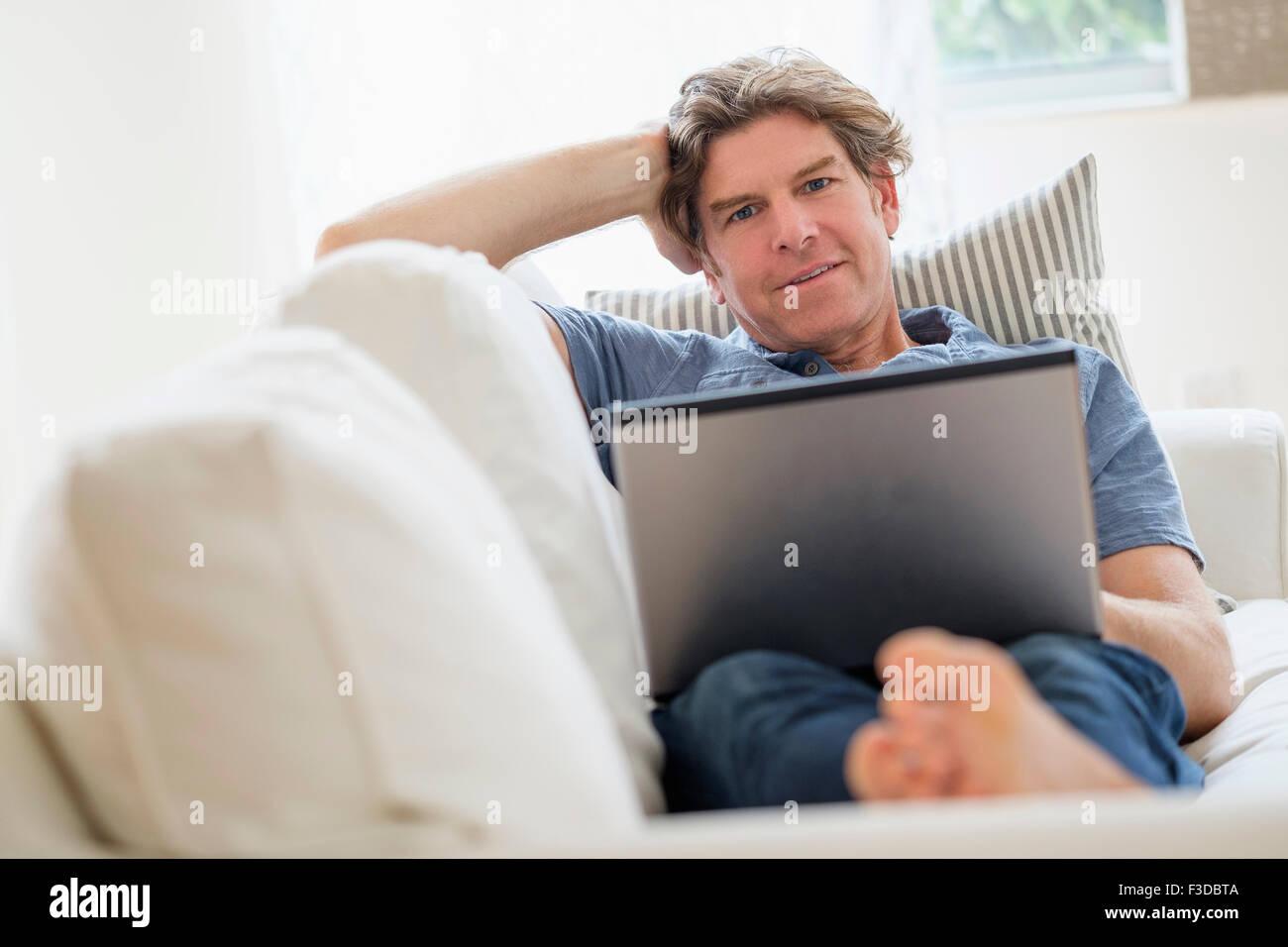 Mature man using laptop on sofa - Stock Image