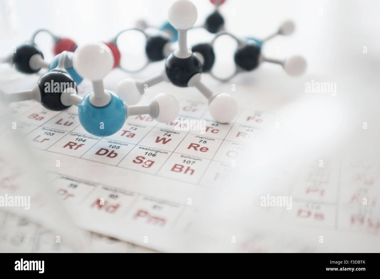 Molecular structure and periodic table on desk - Stock Image