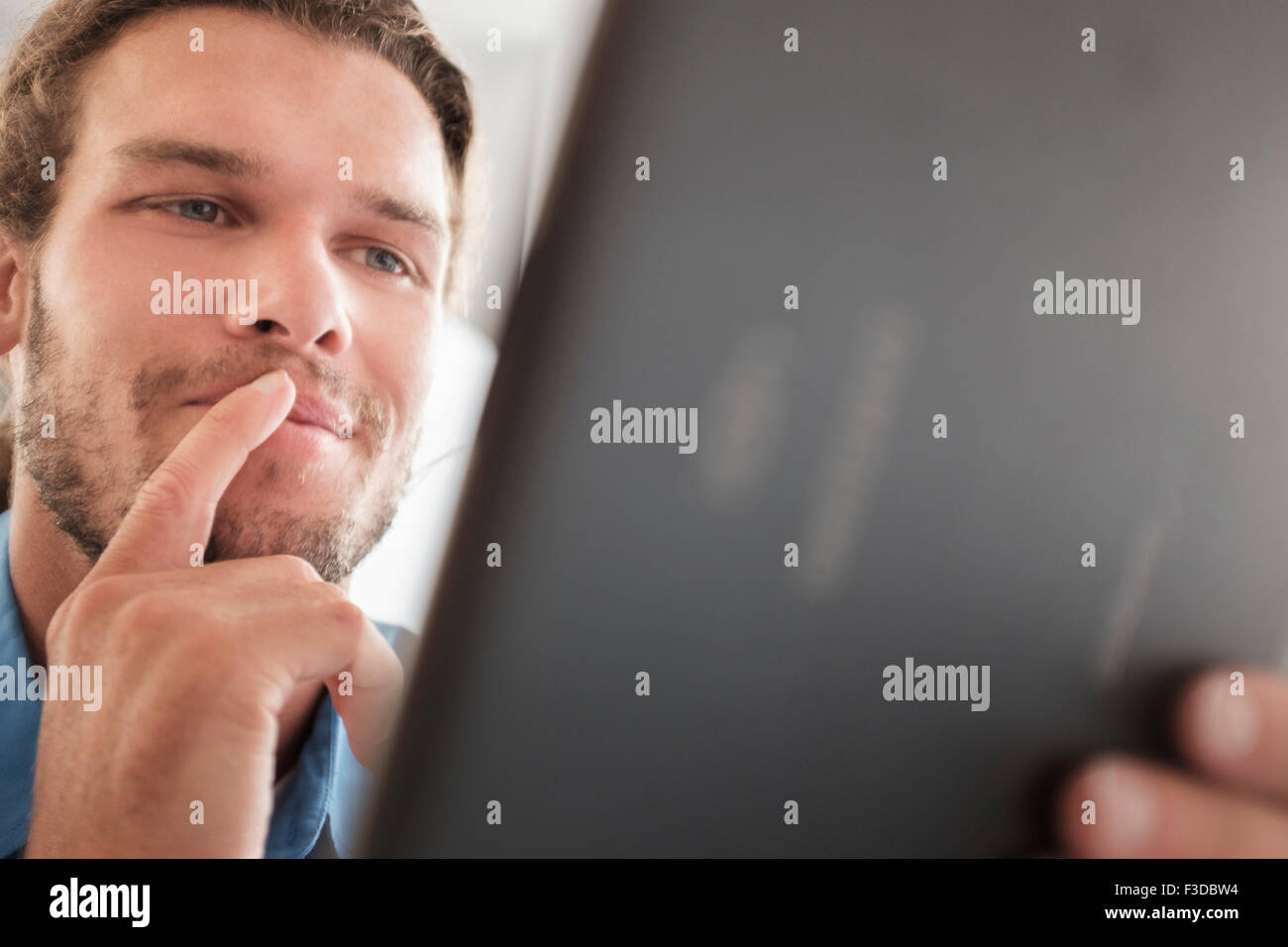 Mid-adult man using tablet pc - Stock Image
