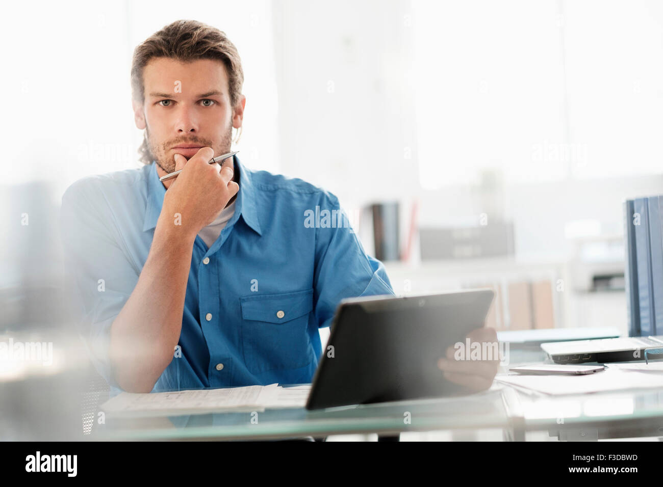 Portrait of mid-adult businessman working in office - Stock Image