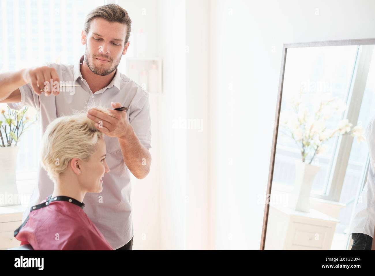 Hairdresser cutting woman's hair - Stock Image