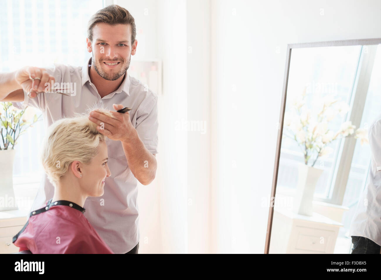 Portrait of hairdresser cutting woman's hair - Stock Image
