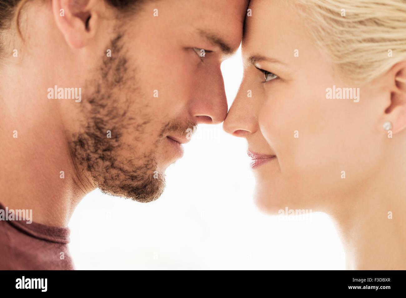 Couple rubbing noses on white background - Stock Image