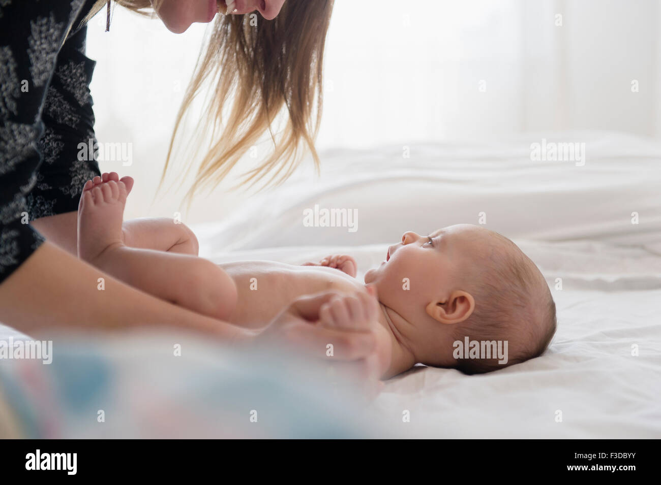 Mother playing with baby girl (2-5 months) on bed - Stock Image