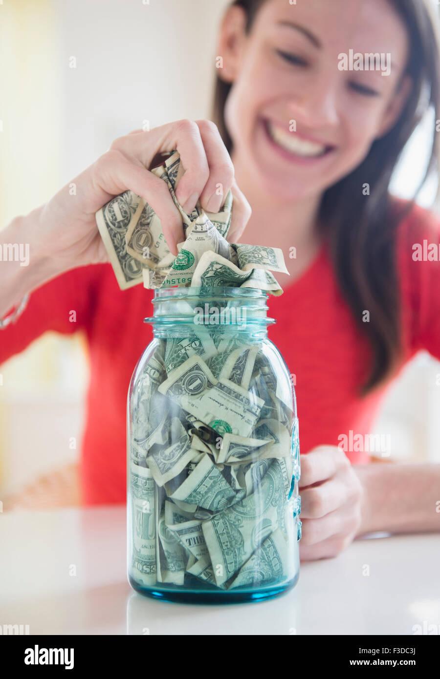Woman putting money into jar - Stock Image