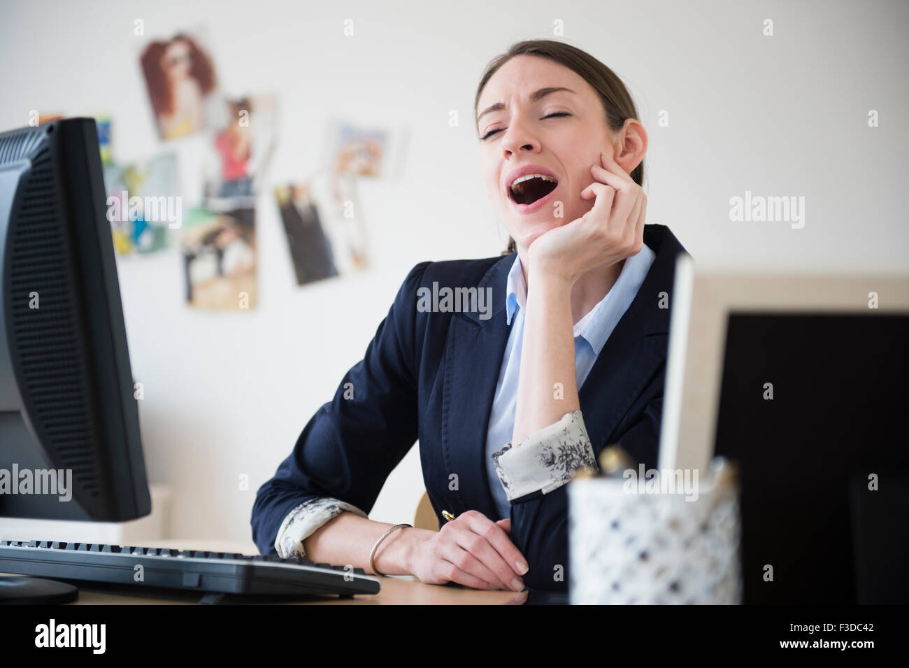 Woman yawning in office - Stock Image