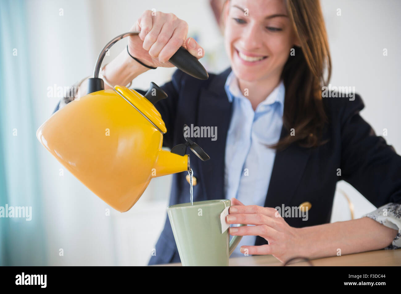 Woman making tea in office - Stock Image