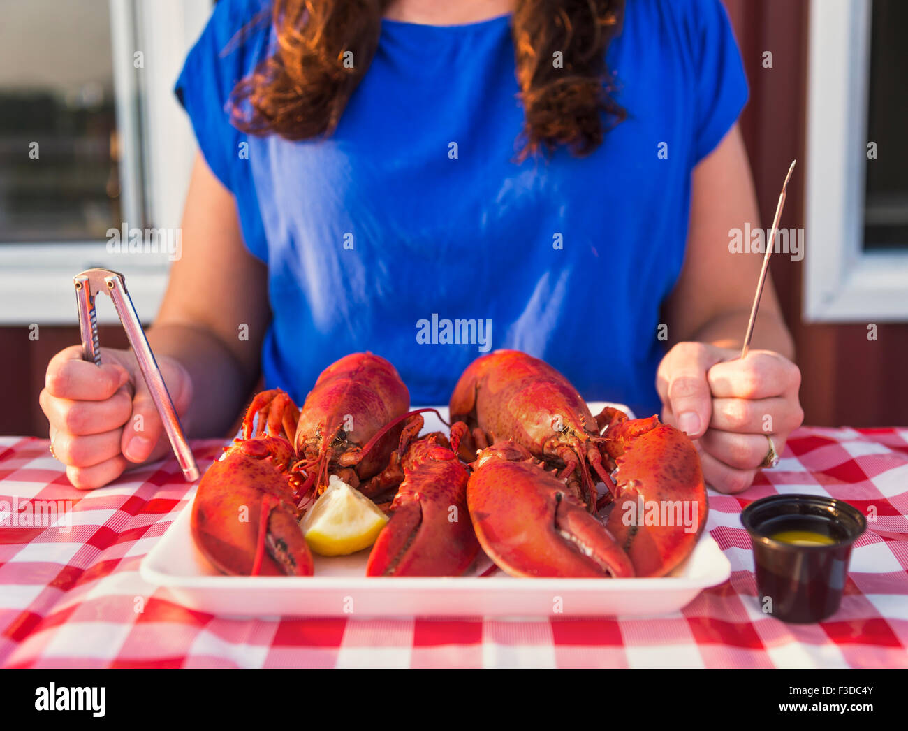 View of table with lobster meal and woman preparing to eat - Stock Image