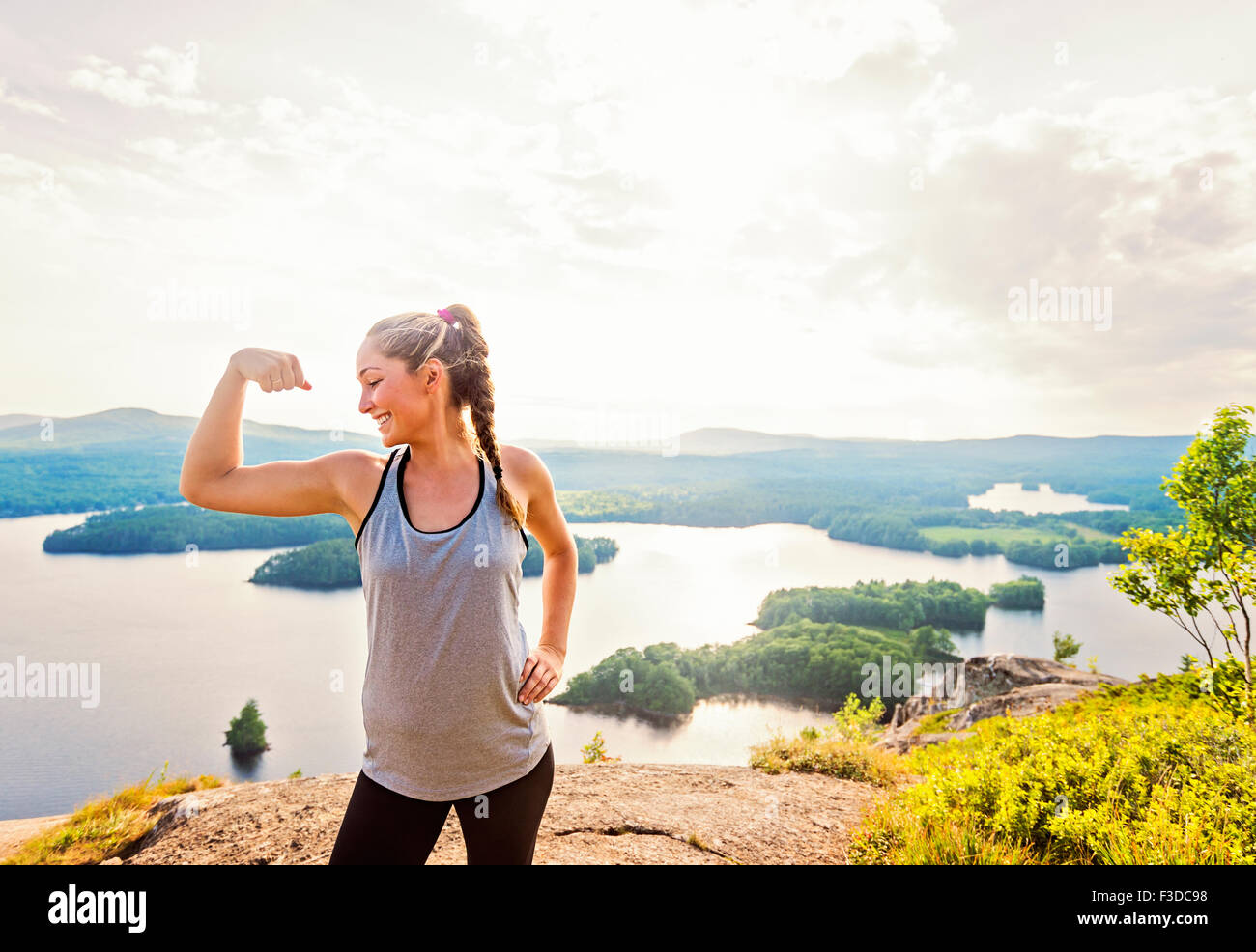 Young woman flexing muscles - Stock Image