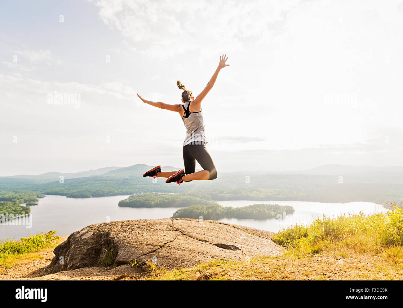 Young woman jumping over mountain top, rear view - Stock Image