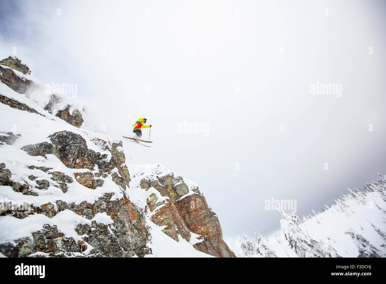 Skier jumping off rocky mountain - Stock Image