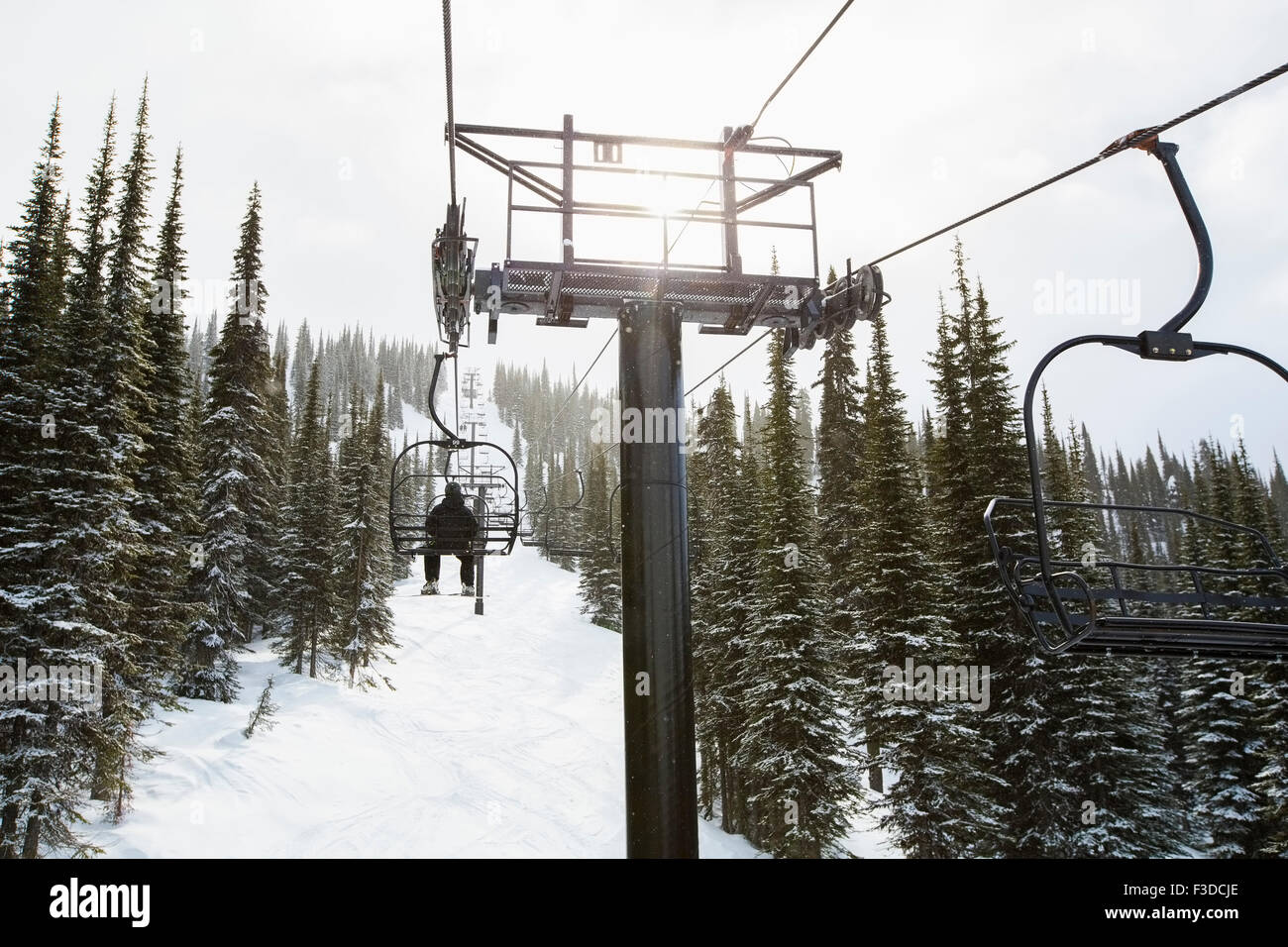 Man in ski lift, rear view - Stock Image