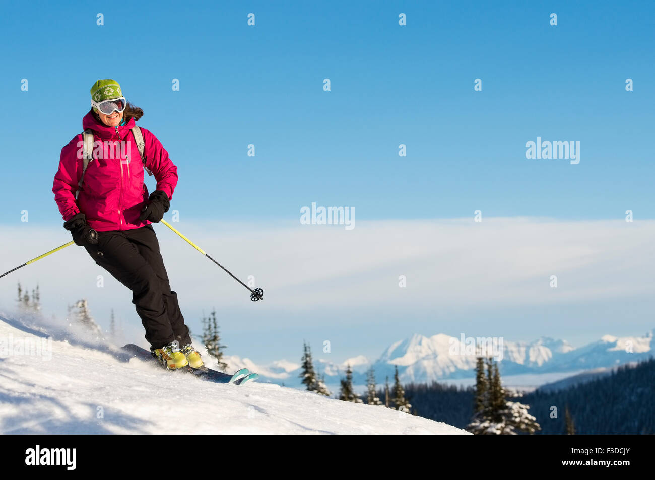 Mature woman on ski slope against sky - Stock Image