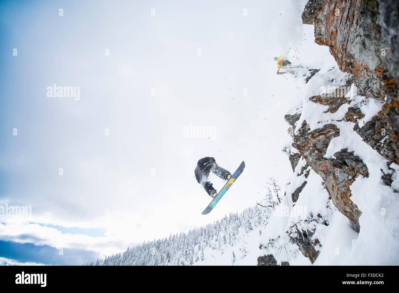 Low angle view of two men jumping from ski slope - Stock Image