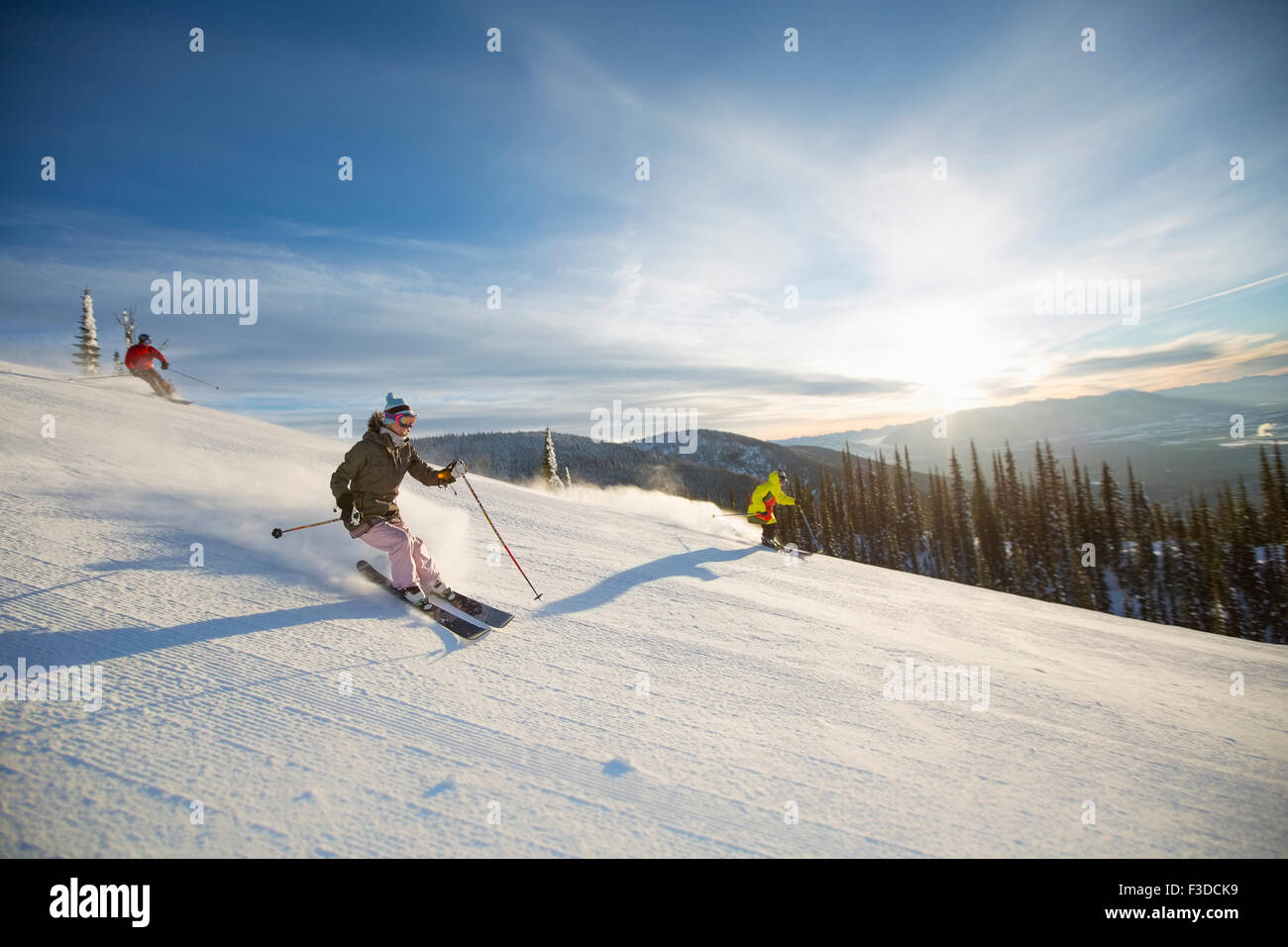 Three people on ski slope at sunlight - Stock Image