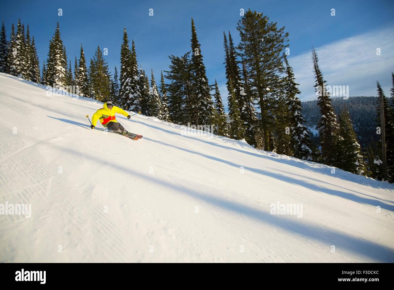 Low angle view of young man on ski slope - Stock Image