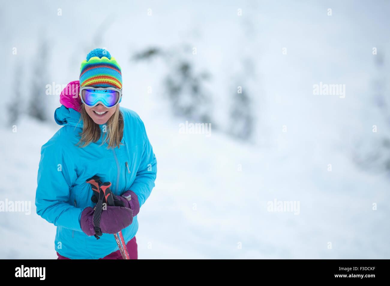 Smiley woman wearing skiwear on ski slope - Stock Image