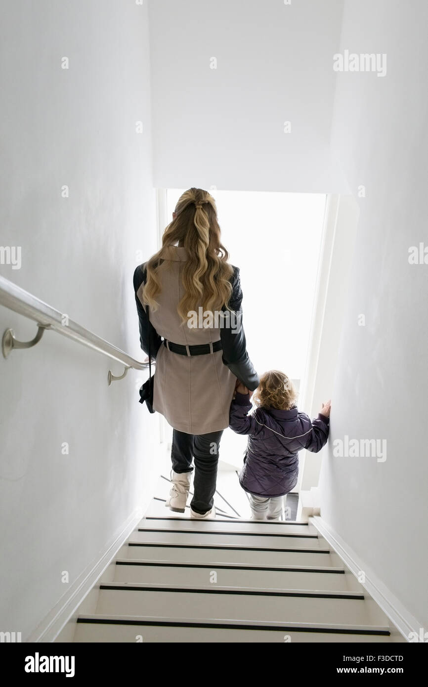 Mother and son (4-5) walking down stairs - Stock Image